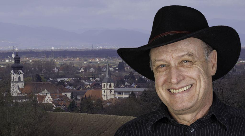 Foto-Collage: Mann mit Hut vor Dorf-Panorama