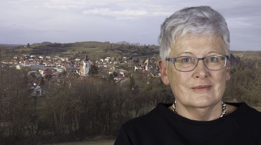 Foto-Collage, rechts Frau mit Brille und kurzen, silbernen Haaren, im Hintergrund Dorf-Panorama