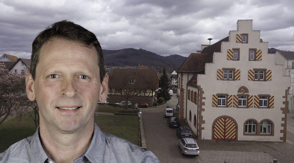 Foto-Collage: Mann mit kurzem, dunklem Haar links, im Hintergrund Historisches Rathaus Friesenheim