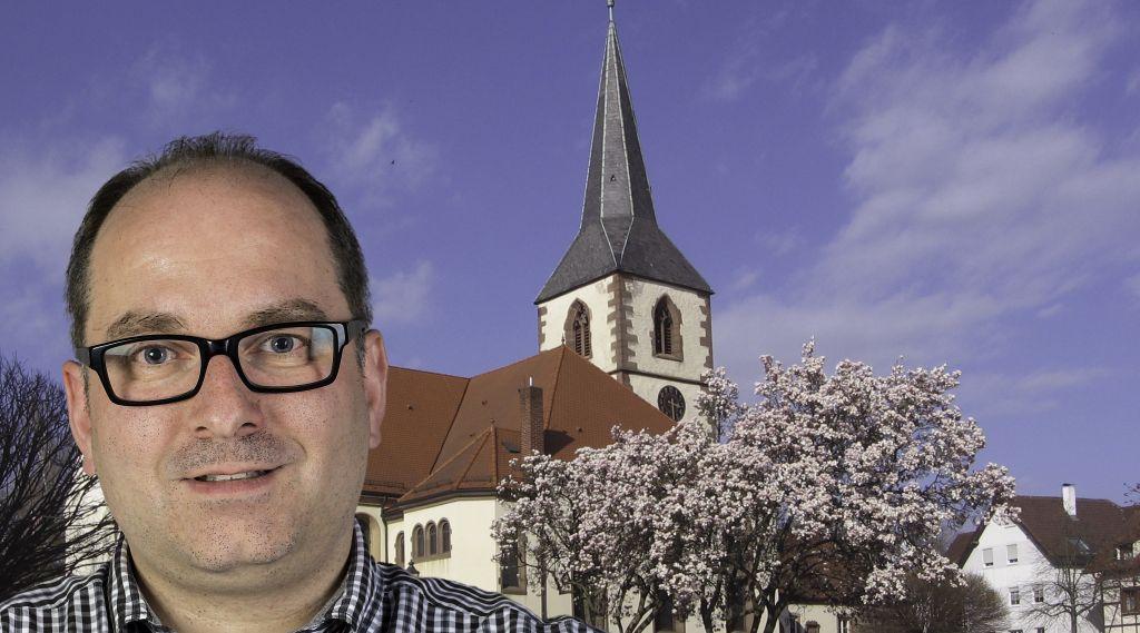 Foto-Collage: Mann mit dunkel-umrandeter Brille, dunklen kurzen Haaren, evangelische Kirche Friesenheim im Hintergrund