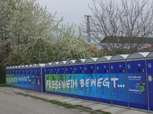 Foto: mehrere blaue Radboxen (abschließbare Fahrradgaragen) in einer Reihe, im Hintergrund Hecken und dahinter das Dach eines Zugwaggons